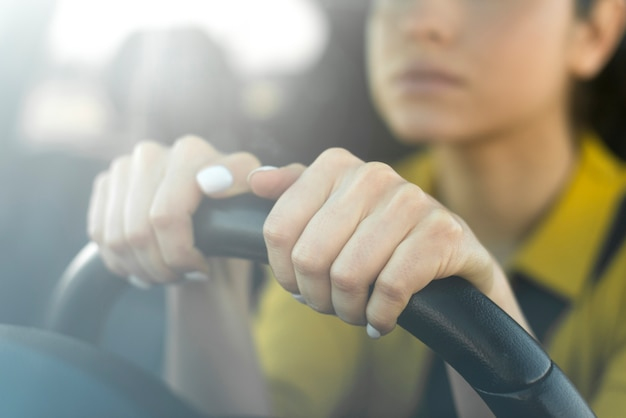 Blurred woman holding her hands on the steering wheel