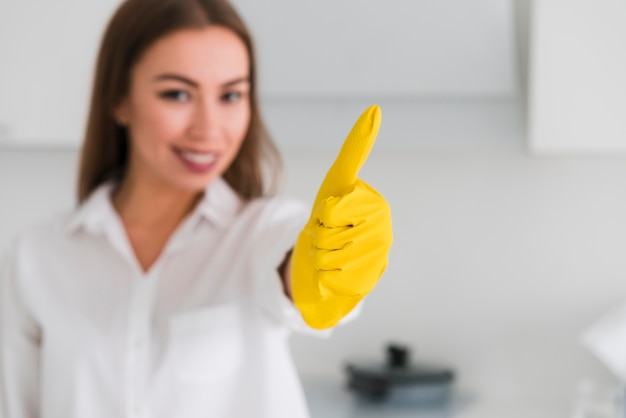 Blurred woman and thumbs up wearing gloves