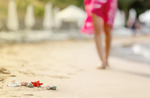 분홍색 드레스를 입고 모래 해변을 걷고 있는 흐릿한 여성, 앞의 조개와 불가사리에 초점, 여행 컨셉