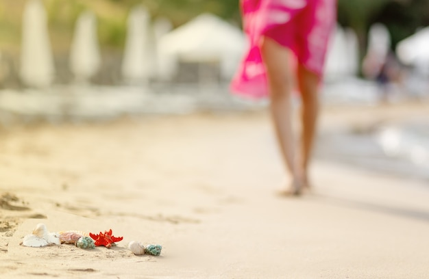 Blurred woman walking on sand privat beach in pink dress, focus on shells and starfish in front, travel concept