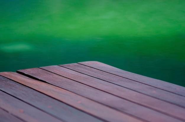 Затуманенное деревянный пол с зеленым размытым фоном
