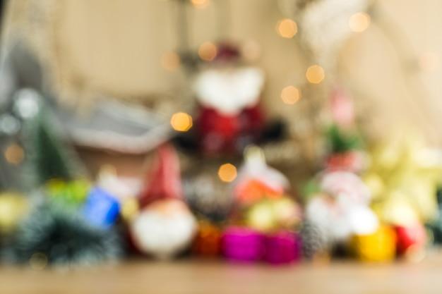 Размытый фон деревянный стол с рождественскими шарами. красные, серебряные и золотые шары, подарочные коробки, фонари, панеттоне, новогодняя елка и другие, чтобы вставить что-то впереди в фокусе.