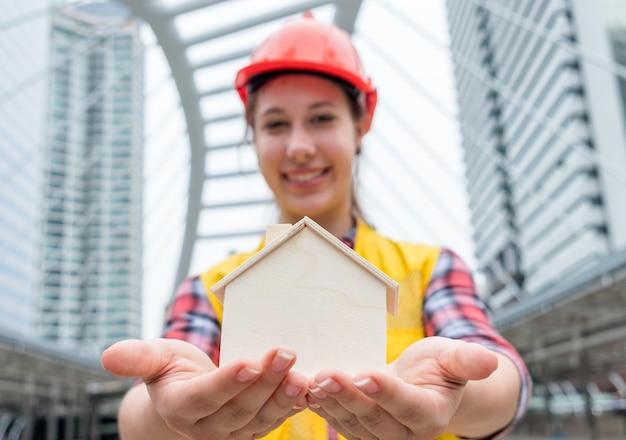 ぼやけた若いエンジニアの女性が街で木造住宅工芸品を与える存在