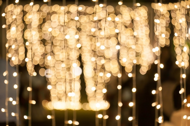 Blurry background of many little light bulb decorations in night party.