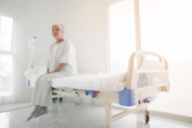 병원에서 침대에 앉아 고위 여자의 흐릿한 배경