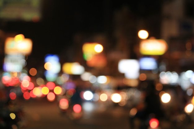 Blurry background of road with roaming cars at night.