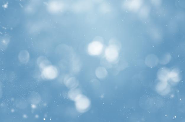 눈송이와 보케가 있는 흐릿한 파란색 배경