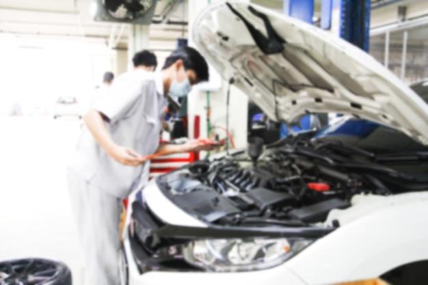 Blurry car repair station and repairman working in the garage. car maintenance or checking of car repair concept.