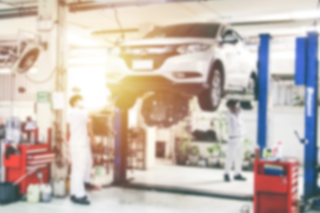 Blurry car repair station and repairman working in the garage