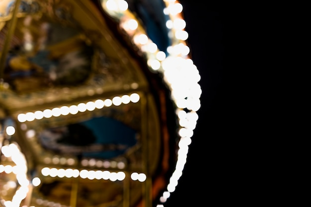 A blurry carousel at the amusement park against black backdrop