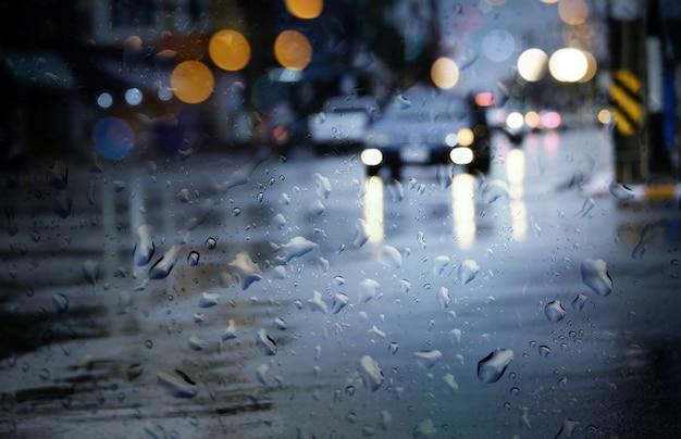 흐릿한 자동차는 밤에 폭우가 내리는 동안 도시의 젖은 도로를 달린다.