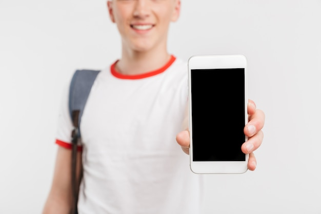Blurry cropped photo of young guy 16-18 years old wearing t-shirt and backpack showing demonstrating black copyspace screen of mobile phone, isolated over white
