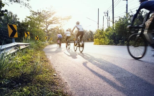 Расплывчатый велосипедист, крутящий педали через резкую кривую с длинной тенью в солнечный день, выборочный фокус на предупреждающих знаках желтой стрелки