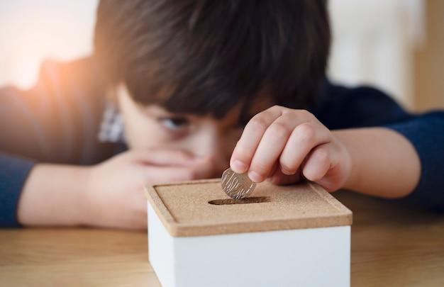 Размытые лицо малыша с мыслящим лицом положить 10 пенсов на копилку, выборочный фокус маленький мальчик делает стека британских денег монеты и подсчета. обучение финансовой ответственности и сохранение на будущее
