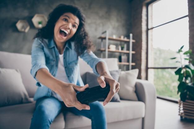 Размытое фокусное фото забавной симпатичной темнокожей волнистой женщины, держащей джойстик геймпада, увлеченного геймера, взволнованного сидящего на уютном диване, повседневной джинсовой одежды