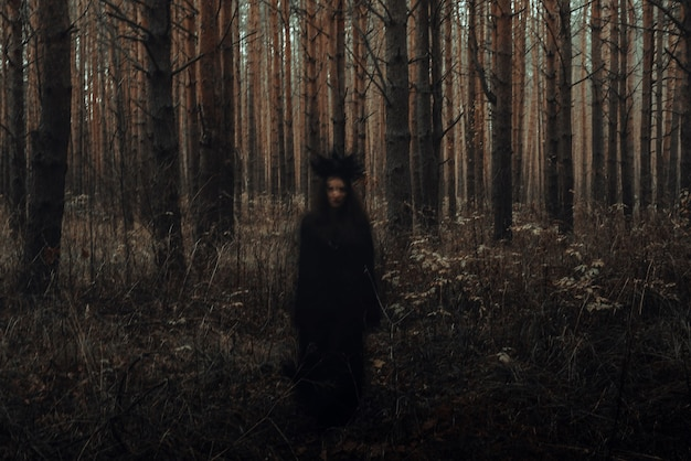 Blurry frightening black silhouette of an evil witch casting spells in a dark forest
