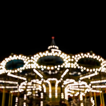 A blurry illuminated carousel in the amusement park at night