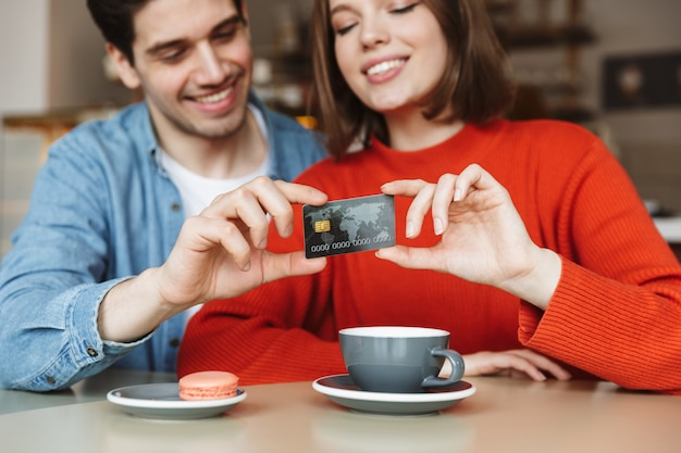 Blurry image of beautiful happy couple man and woman sitting at table in cafe, and holding credit card together