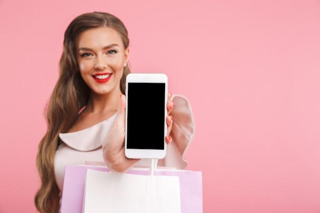 Размытое изображение очаровательной брюнетки, улыбающейся и демонстрирующей экран смартфона copyspace, держа сумки для покупок, изолированные на розовой стене