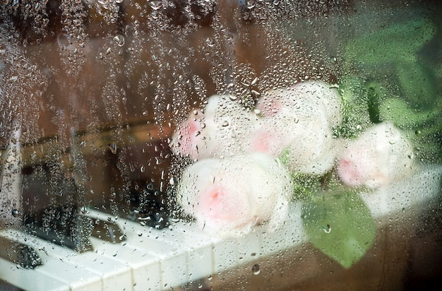 Blurry image through wet glass: pale pink roses are lying on piano keyboard.