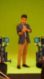 Blurry images of making tv commercial movie video in big green screen background. film crew team working with actor. recording by professional digital camera and lighting set. film behind the scenes