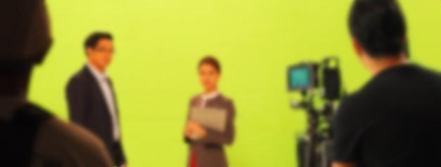 큰 녹색 화면 배경에서 tv 광고 영화 비디오를 만드는 흐릿한 이미지. 배우와 함께 작업하는 영화 제작진 팀. 전문 디지털 카메라와 조명 세트로 녹화합니다. 영화 비하인드 스토리