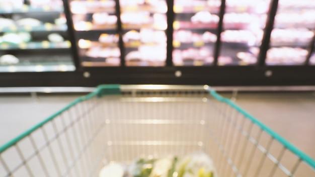 Размытые изображения тележки в супермаркете с точки зрения людей или с точки зрения покупателя.