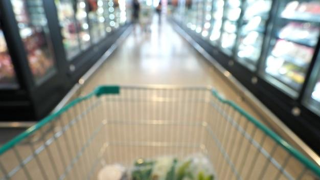 大きなショッピング デパートのスーパー マーケットのカートのぼやけた画像と主観または主観的なカメラ アングル。