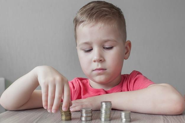 Размытое лицо маленького мальчика, считающее фунтовые монеты на деревянном столе