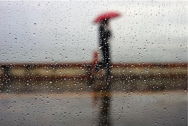 雨の日に濡れた窓の後ろに影男