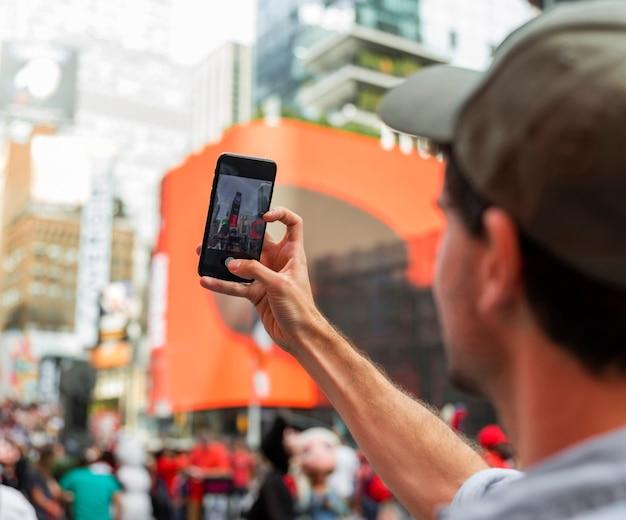 Blurry man face taking selfie in city