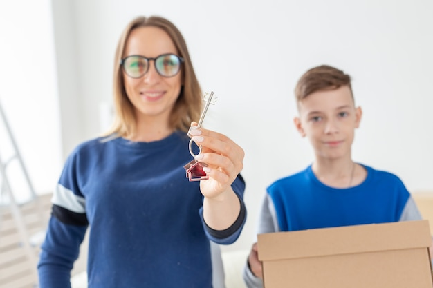 新築祝いの後、ぼやけたママと息子が新しいアパートの鍵を握っています