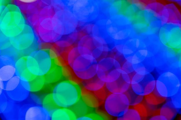 빛나는 조명이 있는 흐릿한 여러 가지 빛깔의 화환. 크리스마스, 새해, 생일 및 결혼식 개념. 흐릿한 배경, 밝은 색 전구, 조명, 화환의 빛