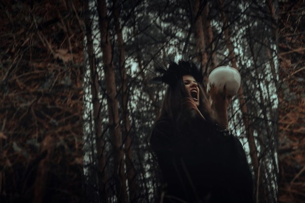 Blurry mystical reflection of a black witch with a skull in her hands performing a satanic ritual in a dark forest