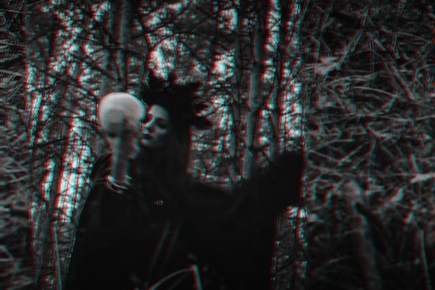 Размытое мистическое отражение черной ведьмы с черепом в руках, выполняющей сатанинский ритуал. черно-белый с эффектом виртуальной реальности 3d глюк