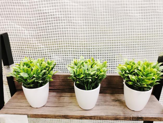 白いプラスチック製のポットの背景に人工緑の植物のぼやけ