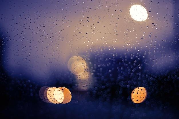 밤에 보케 빛으로 흐릿한 거리 생활. 선택적인 초점으로 강한 비가 내리는 동안 바람막이를 통해 봅니다.