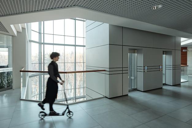 휴식 시간에 큰 사무실 센터 내부 복도를 따라 이동하는 동안 스쿠터를 타고 젊은 활성 사업가의 모호한 개요