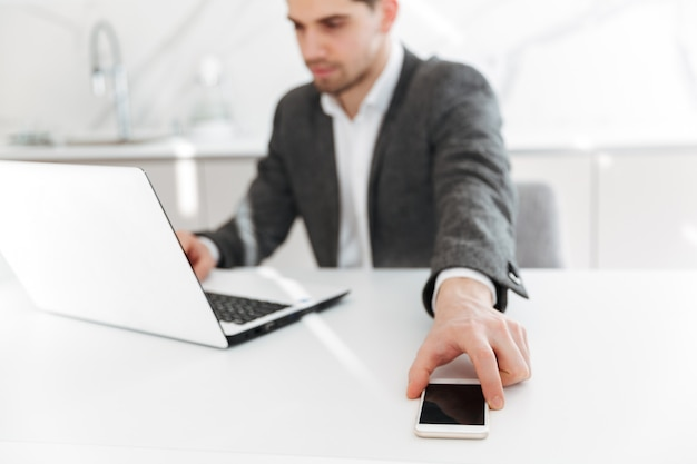 Blurry photo of concentrated businesslike man working on notebook, and taking smartphone from table