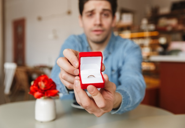 Blurry photo of excited man sitting at table in cafe and proposing to his womanfriend, while demonstrating box with engagement ring