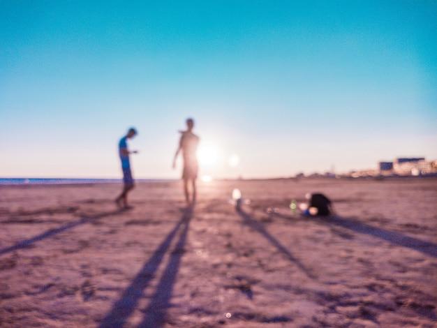 Foto sfocata di persone sulla spiaggia