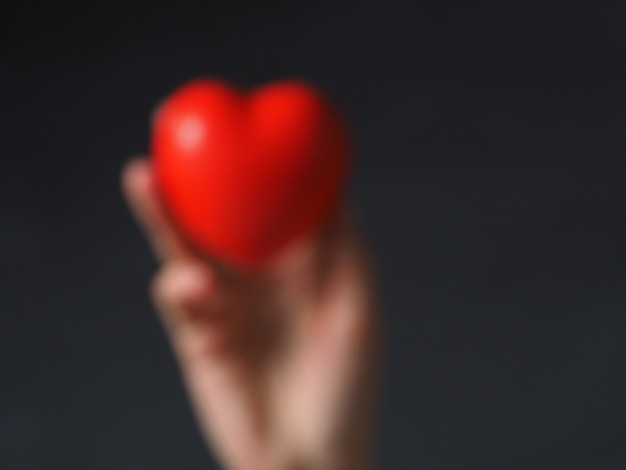 A blurry photo with the outline of a hand holding a red heart. concept of the day of health, care and medicine