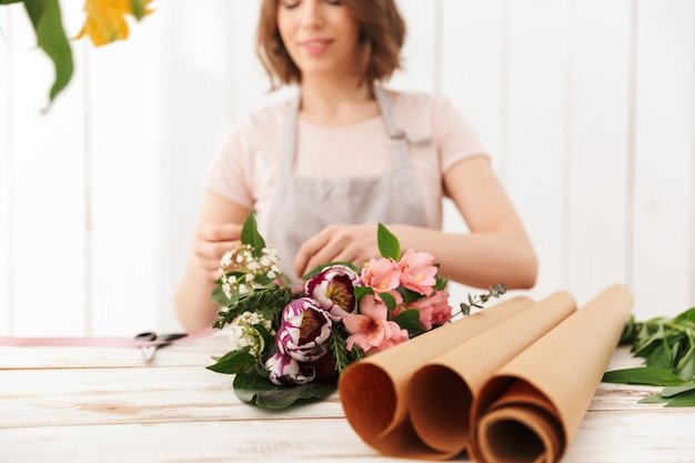 Blurry photo of young florist woman collecting bouquet of different flowers, on table in workshop