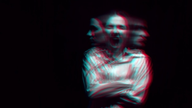 Blurry portrait of a schizophrenic woman with paranoid disorders and bipolar disease on a dark background. black and white with 3d glitch virtual reality effect