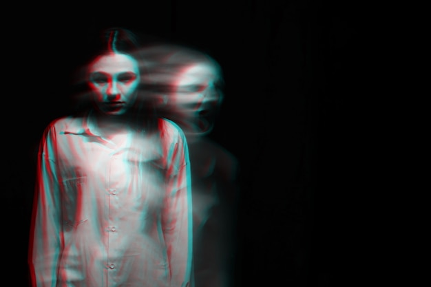 Blurry scary portrait of a witch ghost girl in a white shirt on a dark background. black and white with 3d glitch virtual reality effect