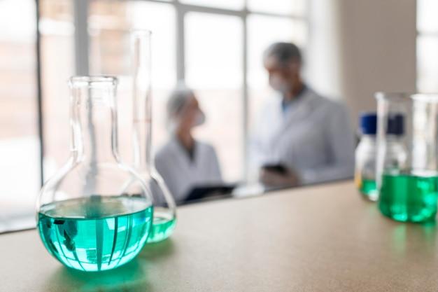 Scienziati sfocati e boccette con sostanze