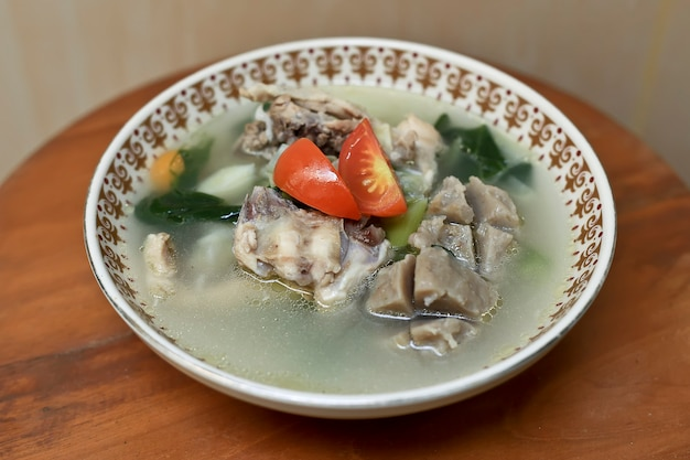 Blurry selective focus tasty sop ayam chicken soup with meatball and tomato cherry on top
