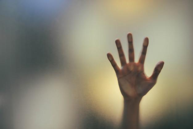 젖빛 유리 뒤에 남자의 흐릿한 그림자 손