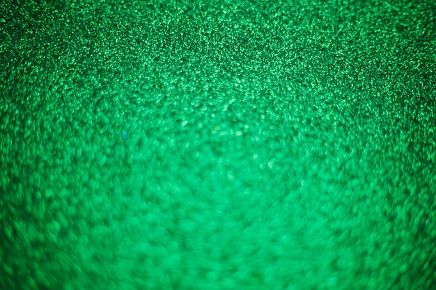 Blurry shimmering background of green sequins. silver glitter, light abstract bokeh texture. drawing design. sparkling wallpaper for christmas. party time.
