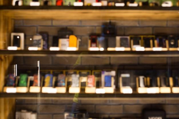 Размытые витрина в вейп-магазине крупным планом. размытая витрина с товарами.